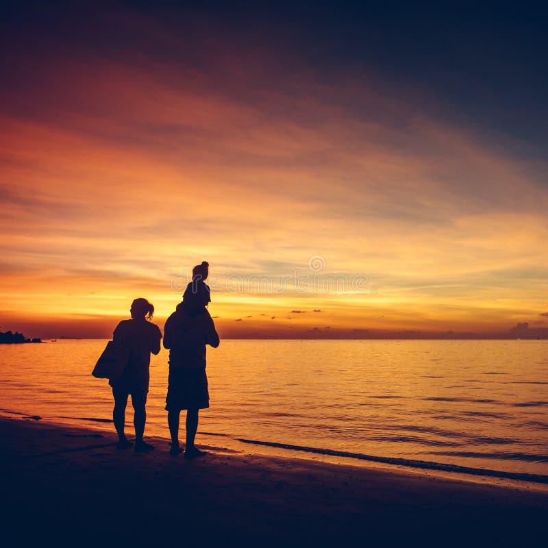 可爱的家庭剪影在日落海滩的 库存照片