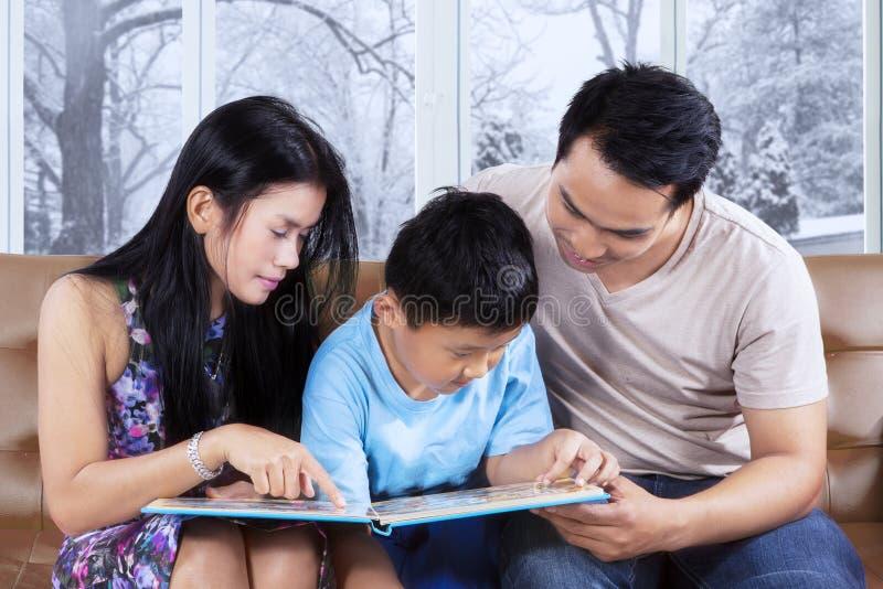 可爱的家庭在长沙发读了故事书 免版税库存图片