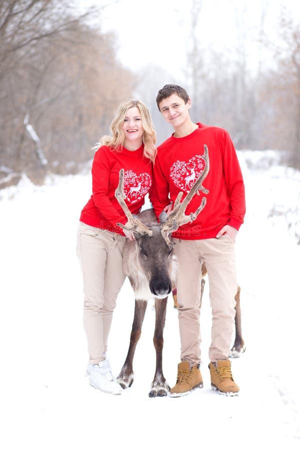 可爱的家庭获得乐趣在冬天公园 人、季节、爱和休闲概念-愉快的夫妇拥抱的和笑的outdoo 免版税库存图片