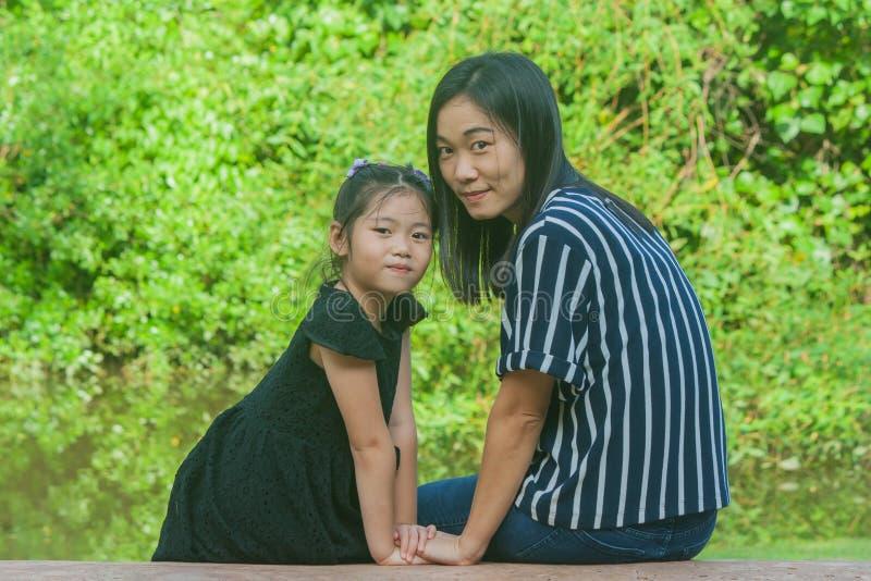 可爱的家庭观念:亚裔坐妇女和的孩子微笑和在具体长的长凳放松 库存照片