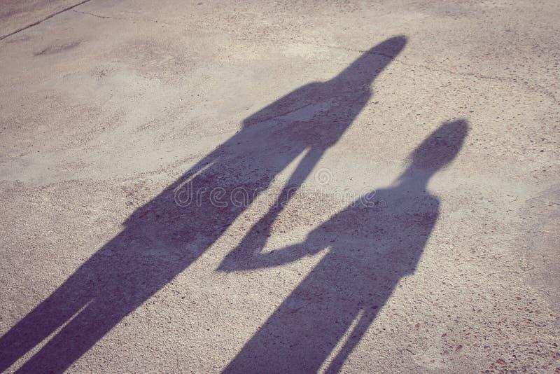 可爱的家庭观念:以站立在水泥地板上和结合在一起使手的妇女和孩子为基础的阴影 免版税库存照片