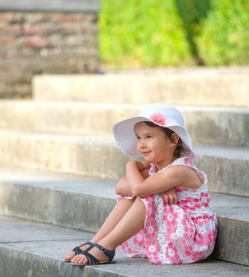 可爱的小女孩佩带的白色帽子坐台阶在温暖和晴朗的夏日 免版税库存图片