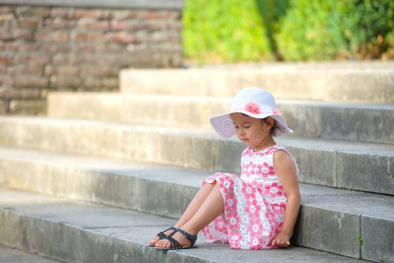 可爱的小女孩佩带的白色帽子坐台阶在温暖和晴朗的夏日 免版税图库摄影