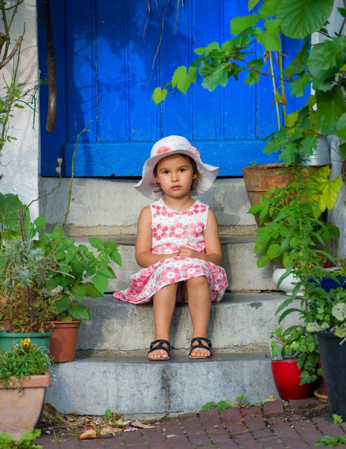 可爱的小女孩佩带的白色帽子坐台阶在温暖和晴朗的夏日 库存照片