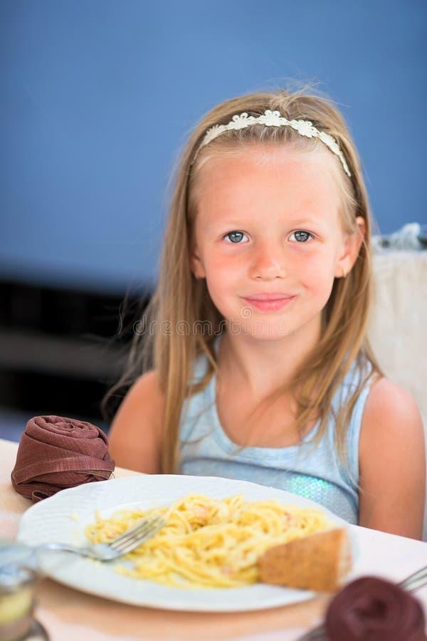 可爱的小女孩吃晚餐在室外咖啡馆 免版税库存图片