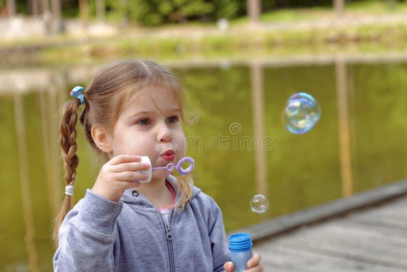 可爱的小女孩吹的泡影在公园 图库摄影