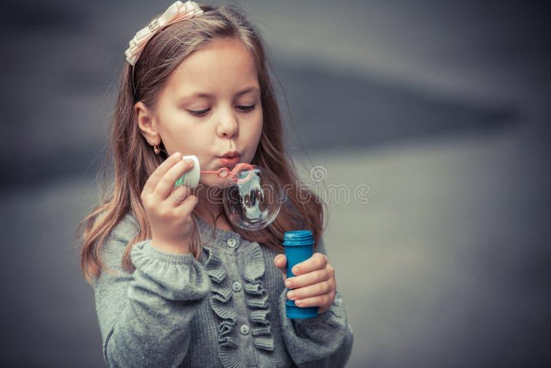 可爱的小女孩吹的肥皂泡 库存图片