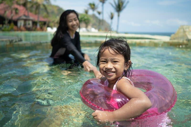 可爱的小女孩和她的母亲游泳 免版税库存图片