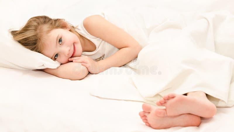 可爱的小女孩在她的床上醒来了  免版税库存照片