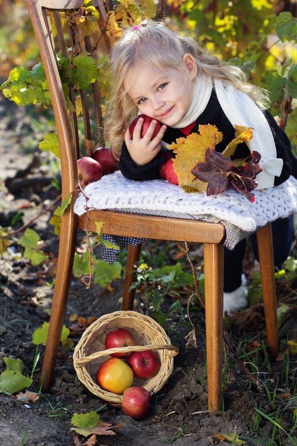 可爱的小女孩用苹果,秋天时间 免版税图库摄影