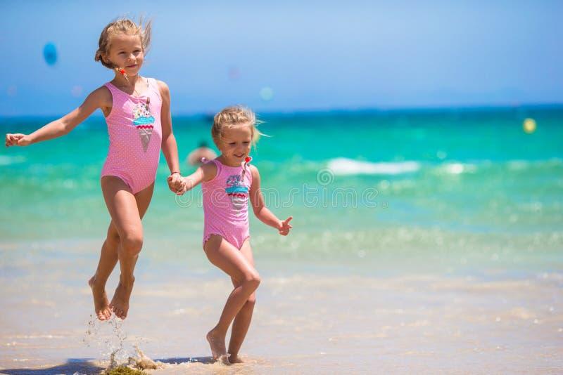 可爱的小女孩获得乐趣在海滩期间 库存图片