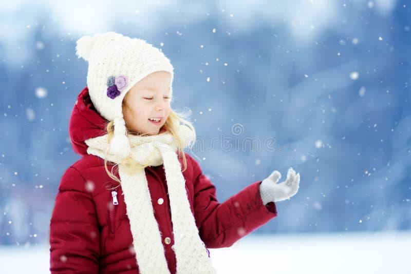 可爱的小女孩获得乐趣在美丽的冬天公园 使用在雪的逗人喜爱的孩子 免版税库存照片