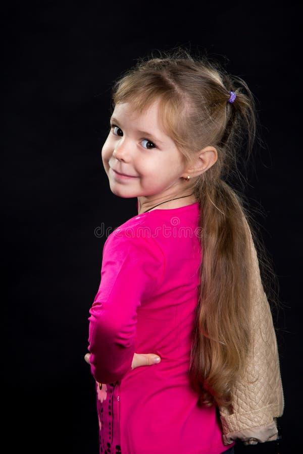 可爱的小女孩,看从后面的模型 黑背景,演播室照片 免版税图库摄影