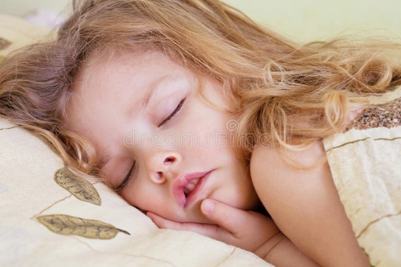 可爱的小孩女孩在床上 图库摄影