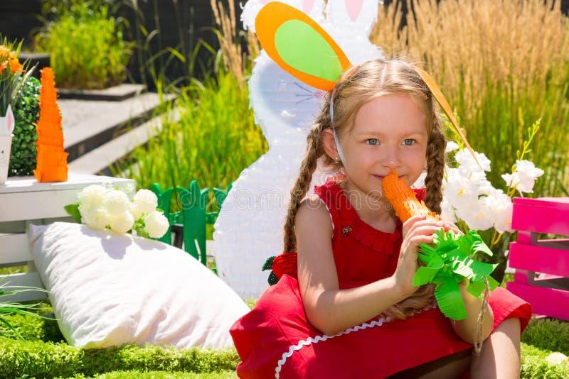 可爱的小孩女孩用在夏天绿色自然背景的红萝卜 免版税库存照片