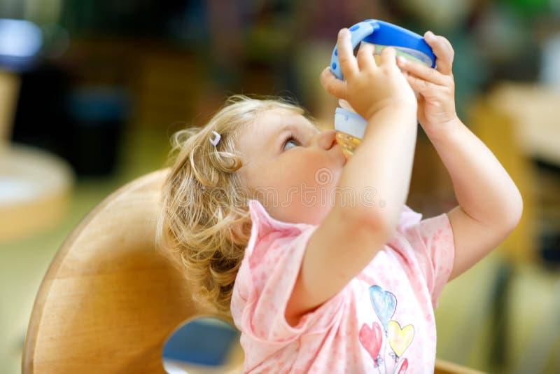 可爱的小孩女孩饮用的惯例牛奶或水从瓶 采取从盘的逗人喜爱的愉快的小孩子食物在托儿 库存照片