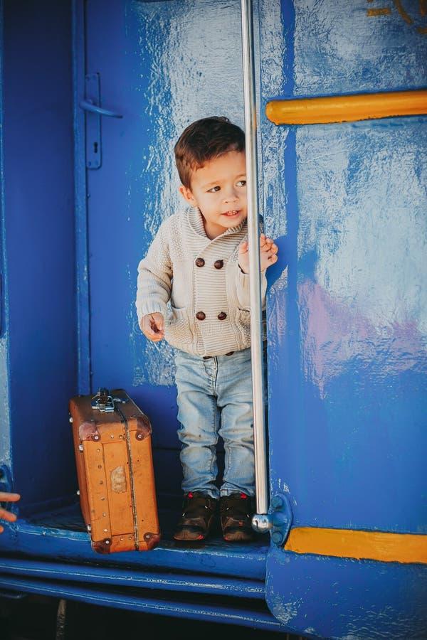 可爱的小孩男孩在一个火车站的红色毛线衣穿戴了 图库摄影
