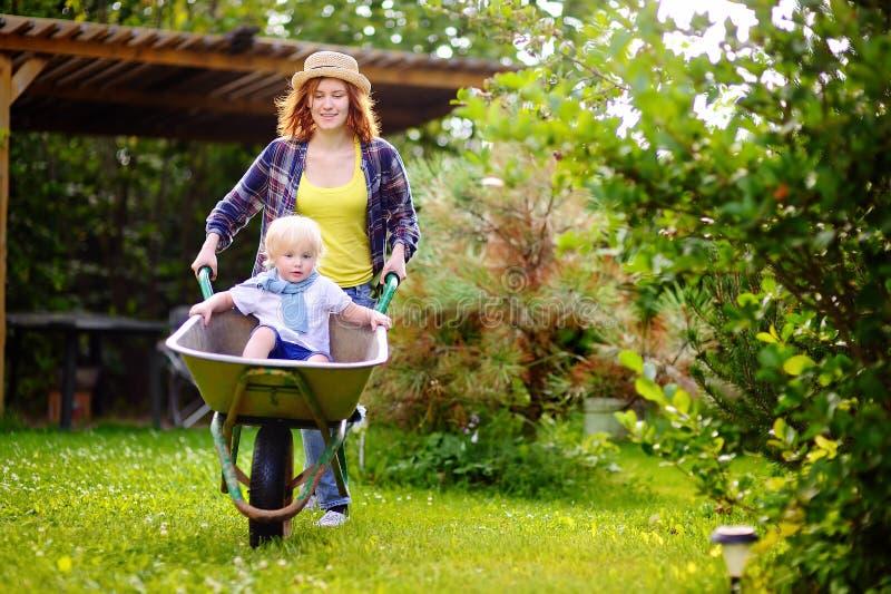 可爱的小孩男孩获得乐趣在推挤由妈咪的独轮车在国内庭院里 免版税库存照片
