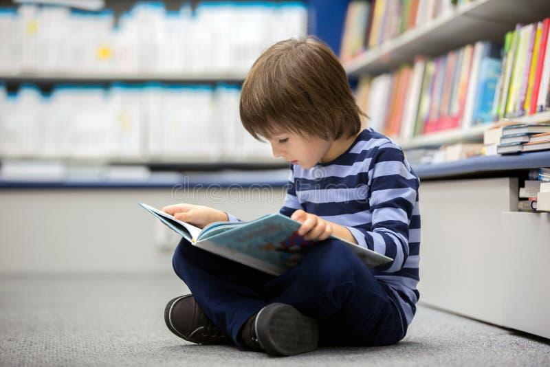 可爱的小孩,男孩,坐在书店 免版税库存照片