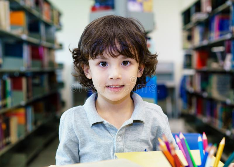 可爱的小孩,男孩,坐在图书馆里,阅读书 库存图片