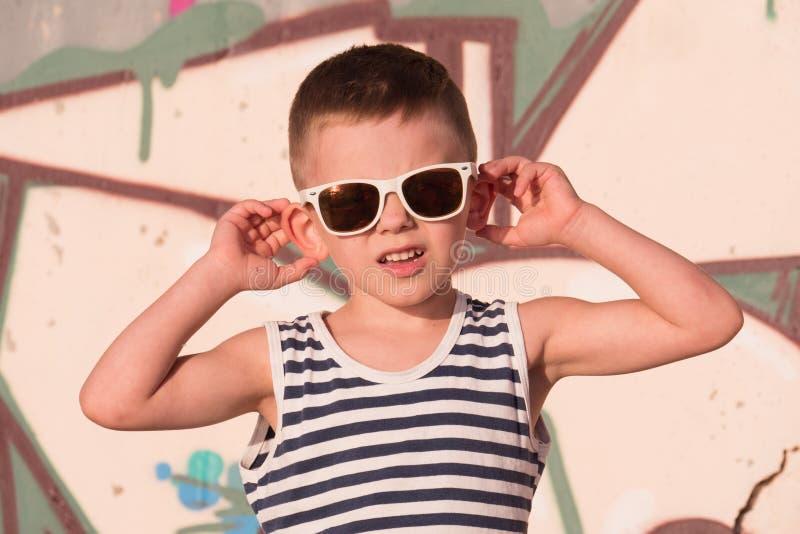 可爱的小男孩佩带的太阳镜和镶边衬衣在街道画背景 免版税图库摄影