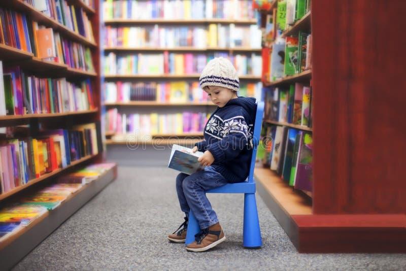 可爱的小男孩,坐在书店 免版税库存图片
