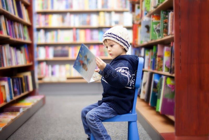 可爱的小男孩,坐在书店 免版税库存照片