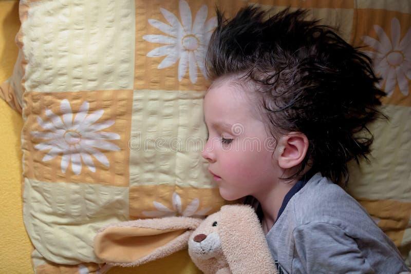 可爱的小男孩,睡觉在与他的玩具熊的晚上frien 库存照片