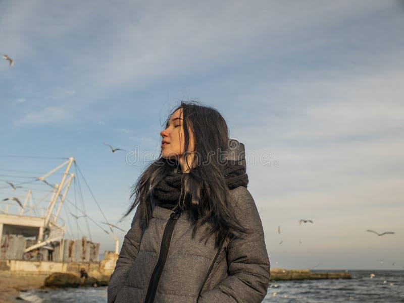 可爱的少女在海滨和天空站立 海鸥在天空腾飞 库存图片