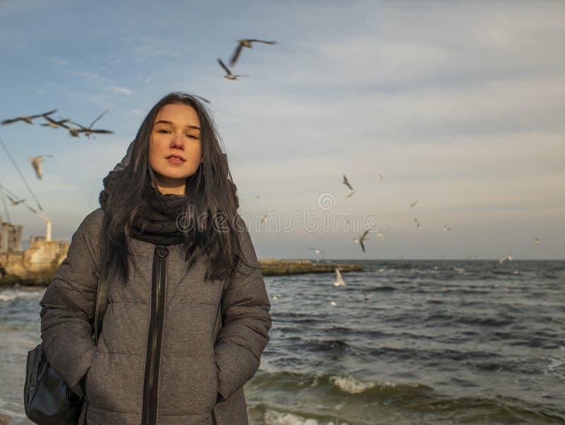 可爱的少女在海滨和天空站立 海鸥在天空腾飞 库存照片