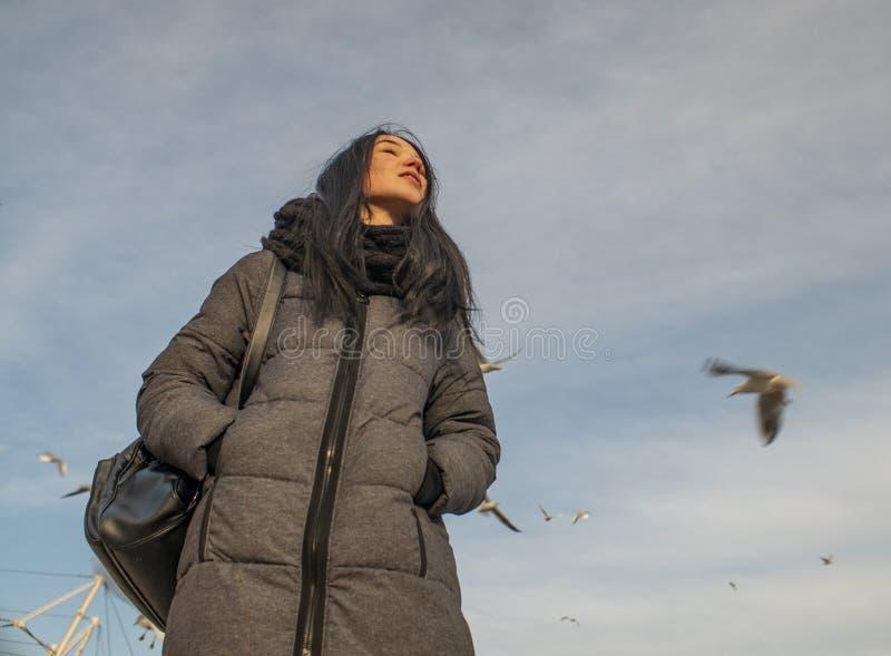 可爱的少女在海滨和天空站立 海鸥在天空腾飞 免版税图库摄影