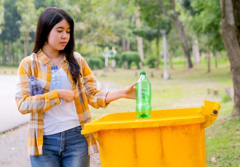 可爱的少女拿着瓶子,把绿色的瓶子扔到花园的黄色垃圾桶 免版税库存照片