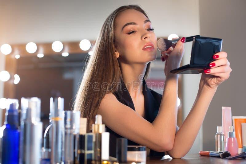 可爱的少妇使用刷子对搽粉她的面孔 免版税库存图片
