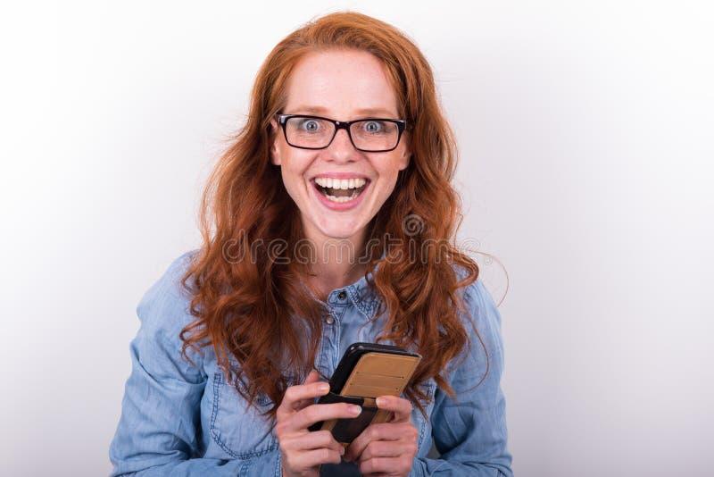 可爱的少妇喜欢什么她在智能手机看见 图库摄影