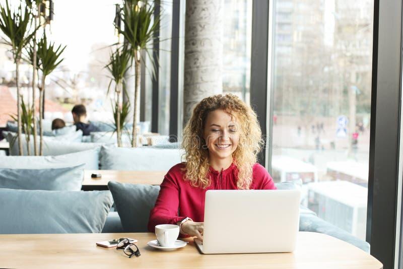 可爱的少妇在与她时兴的膝上型计算机的咖啡店,饮用的热奶咖啡,谈话坐电话,接受去 库存照片