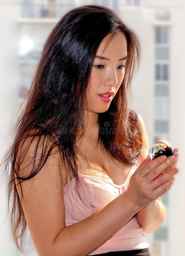 可爱的少妇在她的手上拿着神奇玻璃球 库存图片