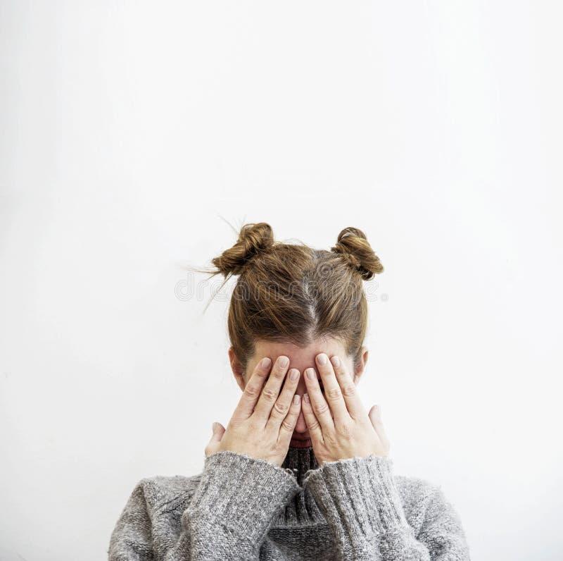 可爱的少妇用她的手盖她的面孔 库存图片