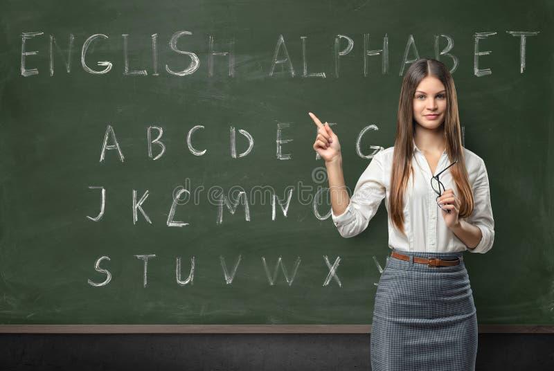 可爱的少妇老师在教室 免版税库存照片