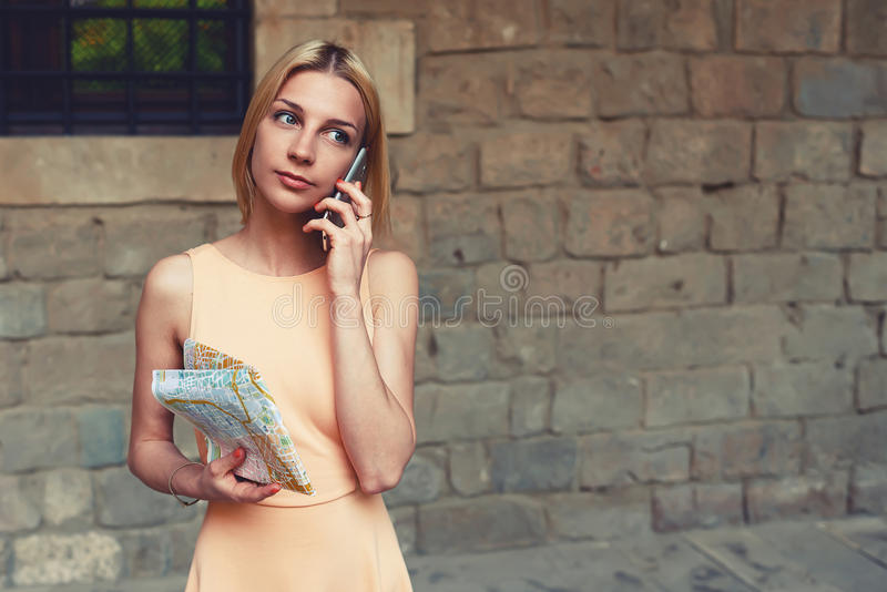 可爱的少妇谈话在手机,当站立在城市街道在夏天时 库存图片