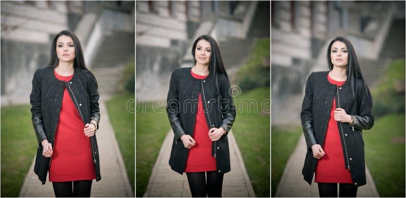 可爱的少妇以冬天时尚射击了与在背景的大厦 黑外套的美丽的时兴的女孩在红色礼服 免版税图库摄影