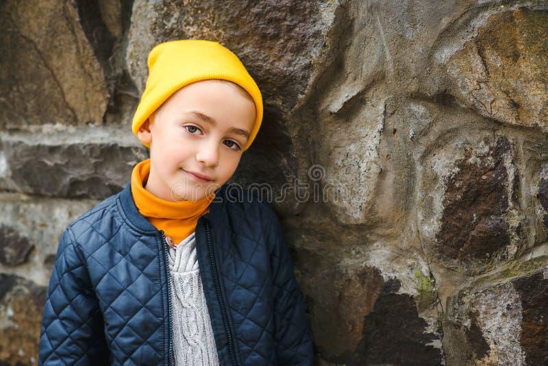 可爱的少年近身肖像 穿着黄色帽子和外套的时髦男孩 秋季时装,复制空间 户外可爱的肖像 库存图片