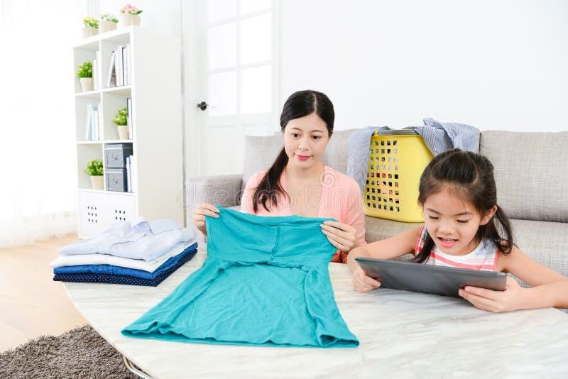 可爱的年轻主妇折叠的衣物 库存图片