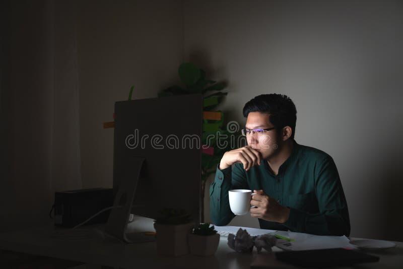 可爱的年轻亚裔人饮用的咖啡坐看在黑暗的夜间运作的感觉的书桌桌手提电脑 免版税库存图片