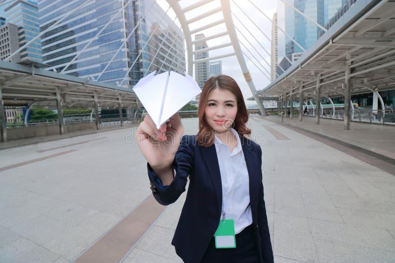 可爱的年轻亚裔女实业家正面图在她的手上的拿着纸飞机 企业概念绘制图象聚焦检查镜扩大化的远见 免版税库存照片