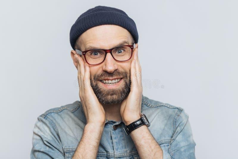 可爱的年轻人画象有厚实的胡子和髭的看与高兴表示,有白色完善的牙,摆在  库存照片