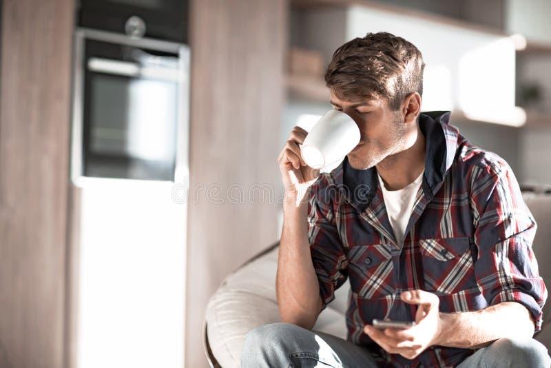 可爱的年轻人饮用的咖啡和读SMS 库存图片