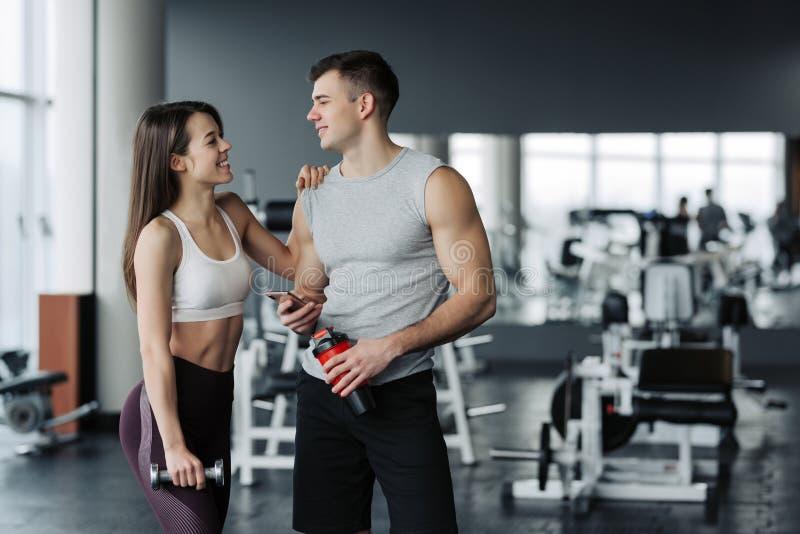 可爱的年轻体育人民拿着瓶水,谈话并且微笑着,当休息在健身房时 免版税图库摄影