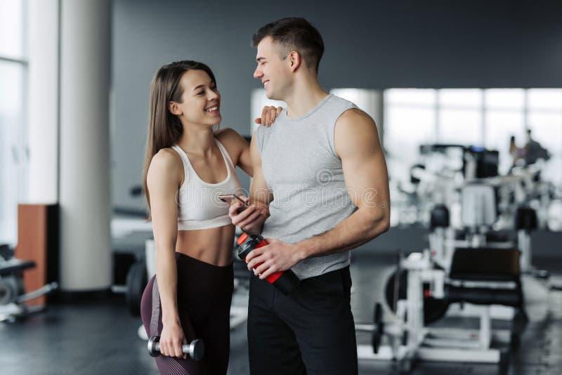 可爱的年轻体育人民是谈话和微笑,当站立在健身房时 库存图片