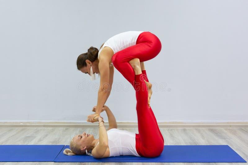 可爱的年轻体育女孩一起做着瑜伽 小组训练 概念健康生活方式 免版税库存照片