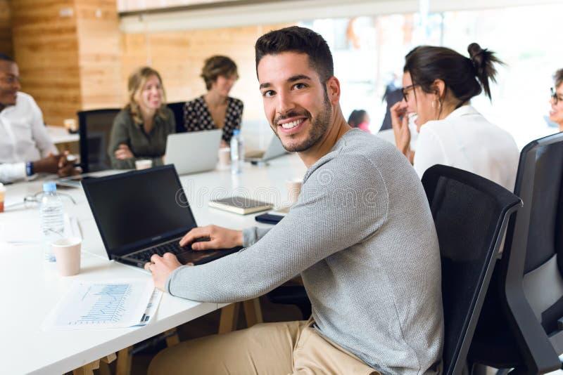 可爱的年轻商人与膝上型计算机一起使用,当看在coworking的地方时的照相机 免版税库存照片